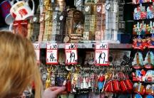 the back of a woman's head as she rifles through some British souvenir knick knacks