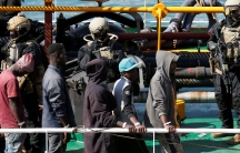 Migrants are shown in the near ground walking in a line as they disembark from a merchant ship with armed soldiers behind them.