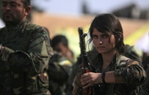 woman wearing military fatigues holds a gun