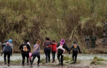 A group of migrants cross a shallow river and met with border agents in green uniforms.