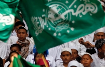 Young boys wearing white robes and caps stand behind green flag with Arabic script.