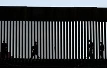 Shadow of patrolmen along slated wall at US border.