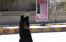 Two women wearing black veils walk outside past a sign with Arabic text.
