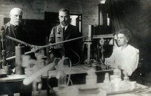 A black and white photo showing three scientists in an old looking laboratory.
