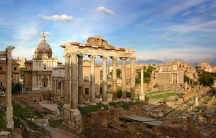Columns, foundations, and churches spread out around the city of Rome on a sunny day.