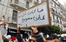 A protester holds up a sign in Arabic writing.