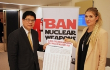 Two diplomats stand in front of a sign that reads ban nuclear weapons