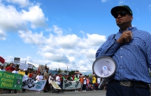 A man with a bullhorn stands in front of a line of protesters