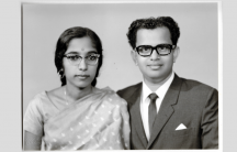 An Indian woman in a sari and glasses and an Indian man in a suit and glasses sit for a portrait.