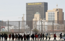 """A line of people stand along a fence. Behind them, a high rise office tower reads """"Wells Fargo"""""""
