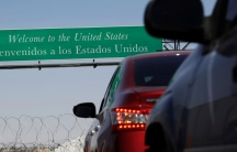 """A sign says """"Welcome to the United States"""" as cars line up underneath it"""