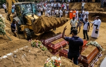 A man waves a backhoe as it lifts dirt to drop onto four caskets laid out in a row