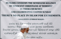 """A man walks by a large banner that reads """"Muslims condemn the senseless killings of innocent Christians at worship in their churches and celebrating Easter Sunday. There's no place in Islam for extremists."""""""