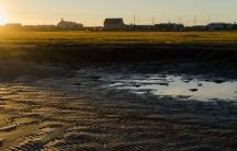 A person walks through a puddle in Shismaref, Alaska.