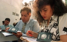 A man and a woman fill out forms with Mexican passports in the frame