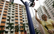 A woman works out with apartment buildings behind her