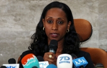 Ethiopian transport minister Dagmawit Moges is shown sitting at a chair behind several microphones.