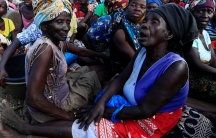 Women sit on the ground wearing colorful head wraps waiting for aid.
