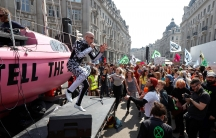 A man on a platform performs to a crowd of protestors