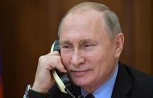 a smiling vladimir putin on the phone