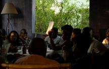 A group of young Haitians are shown sitting around a table in a room without glass in the windows.