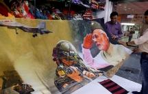 Trader displays sari with image of modi with his military tanks