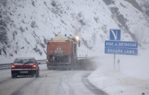 A red car and a large salt truck drive on a snowy road next to a mountain.