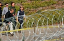 A woman and three men walk next to a fence with razor wire.