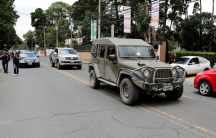A green military truck drives on a road.