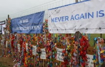 A fence strung with signs and paper cranes