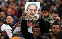 A man holds a poster of eastern Libyan military commander Khalifa Haftar