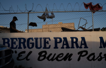 A man is silhouetted against a fence topped with razor wire. People have clothespinned clothing on the fence to dry.