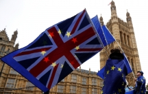 Anti-Brexit protesters wave EU and Union flags outside the Houses of Parliament