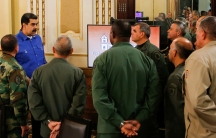 Venezuela's President Nicolás Maduro is shown wearing a blue shirt standing among a group of military authorities.