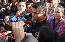 Venezuelan opposition politician Leopoldo López is shown in a crowd of people speaking into several microphones.