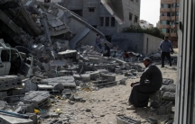 A man sits looking at a building in ruins.