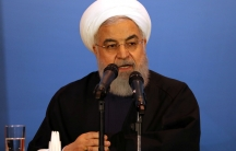 Iranian President Hassan Rouhani is shown sitting at a table with a glass of water speaking behind two microphones.
