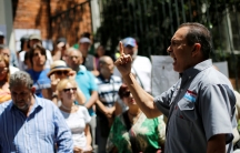 Lawmaker Richard Blanco is shown with his right hand rised and finger pointed up while giveing a speech.