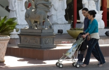 An Asian couple pushes a baby stroller on their way into a shopping mall.