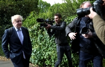 Boris Johnson is shown walking with his hands in his pockets and a gaggle of photographers around him.