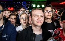 Several young men are shown looking past the camera with some wearing glasses.