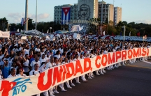 Cubans hold a sign of unity in red lettering on May Day.