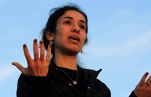 Nadia Murad gestures with her hands against a blue sky.