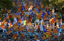 People wave Catalan flags during a demonstration organized by Catalan pro-independence movements following the imprisonment Jordi Sanchez and Jordi Cuixart, in Barcelona, Oct. 21, 2017.