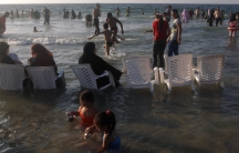 Women wearing headscarves sit in chairs at a public beach in Alexandria, Egypt