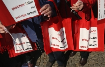 """Women hold bags and signs that read: """"Same pay for same work"""" at a rally for equal pay in Berlin, Germany, 2015."""
