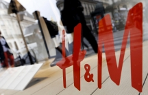 People are seen walking past an H&M store through the reflection in the glass.