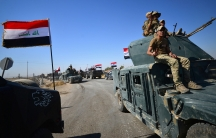 Members of Iraqi federal forces drive along desert roads in Kirkuk with Iraqi flags flying.