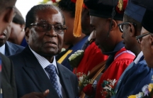Zimbabwe President Robert Mugabe stands center with a blue suit and tie shaking the hands of college graduates.