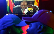 Two men in the foreground wearing baseball hats watch Zimbabwean President Robert Mugabe on a TV.